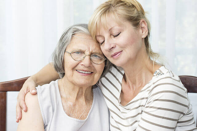 daughter embracing aging mother