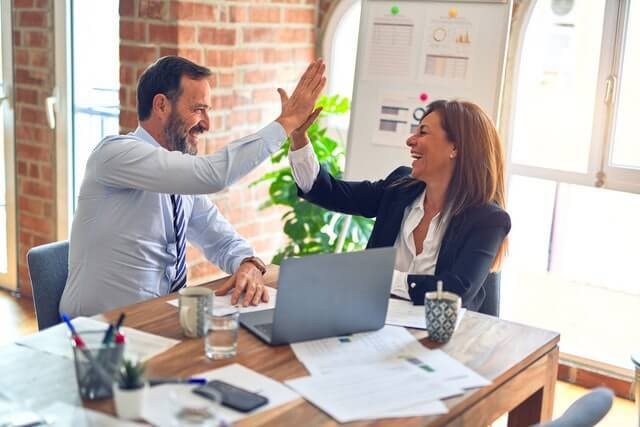 man and woman business executives high fiving